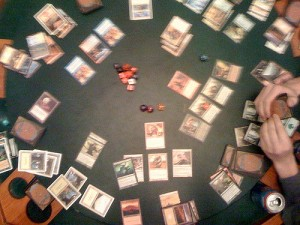 Magic; The Gathering game in progress with cards and dice on a tabletop